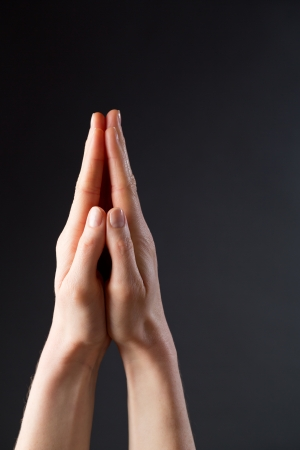 Praying hands of a young woman over a dark background.