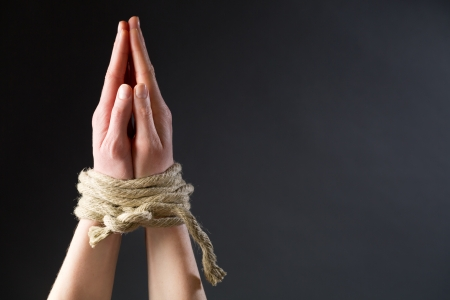 christian youth: Two hands of a young woman in position for prayer tied with a rope.