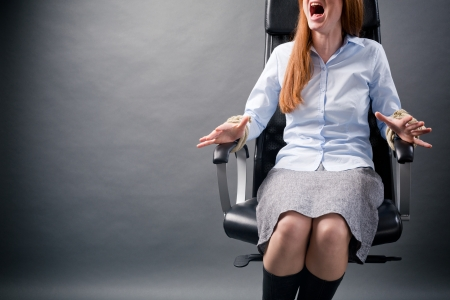 A young businesswoman tied to an office chair screaming for help.