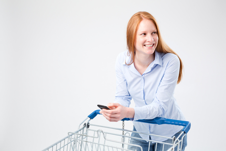 A young woman with red hair doing grocery shopping with a list on her smartphone. photo