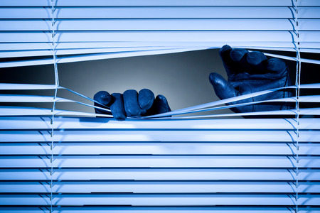 prying: Two hands of a thief or a stalker opening closed window shutters at night. Stock Photo
