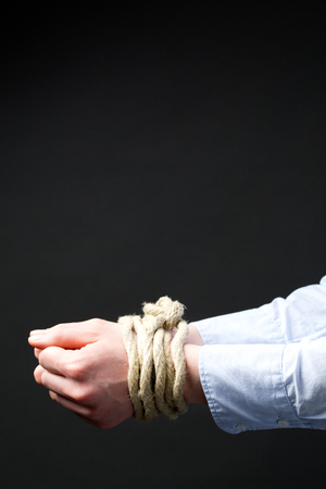 abducted: Two hands of a business person tied up together with a rope.