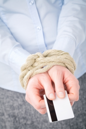 Businesswoman with tied up hands holding a credit card - debt metaphor. photo