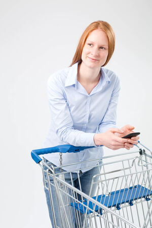 A young Caucasian woman with a shopping cart and a mobile phone in her hands. photo