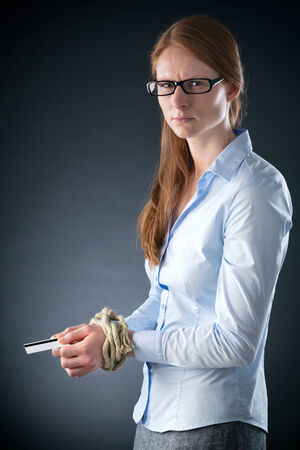 A sad young businesswoman with tied up hands holding a credit card and looking at the camera. photo