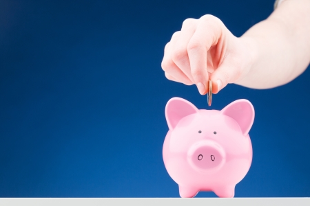 Hand of a woman inserting a one dollar coin into a pink ceramic piggy bank.  photo