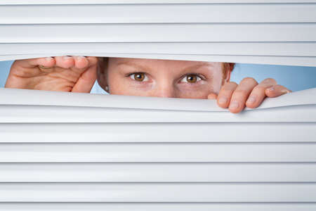 A young woman peeking through closed venetian blinds or shutters. photo