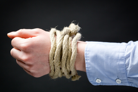 suppressed: Closeup image of two hands of a businesswoman tied up together with a rope.