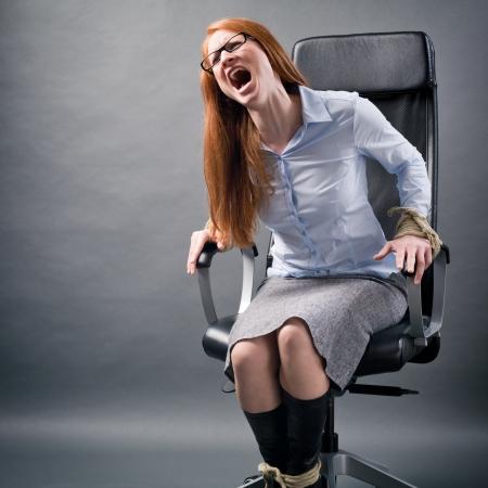 gefesselt: Ein verzweifelter Geschäftsfrau bis zu einem Bürostuhl um Hilfe schreien gebunden. Lizenzfreie Bilder