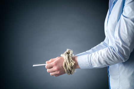 overdraft: Side view of a young businesswoman holding a credit card with hands tied up with a rope. Stock Photo
