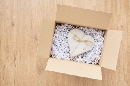 Open parcel box with a heart shaped Valentines Day gift inside it. photo