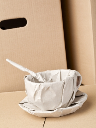 A fragile coffee cup wrapped in packaging paper, photographed over brown carton boxes. Stock Photo