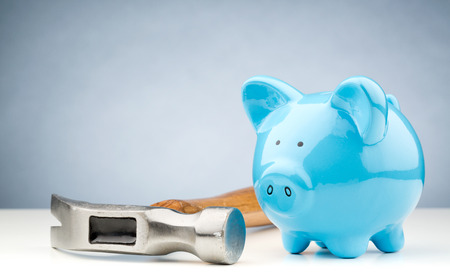 A large hammer lying next to a blue piggy bank on a white desk surface with copy space above it.