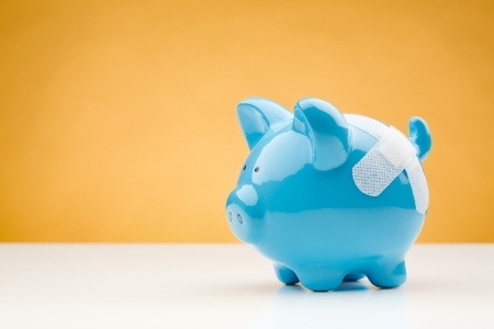 A blue piggy bank with a bandage standing on a white desk surface with an orange background. Stock Photo