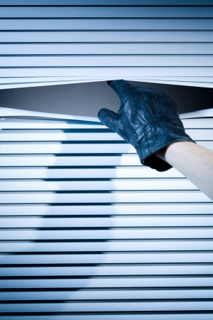 prying: Thief or a stalker opening window shutters to peek through. Stock Photo