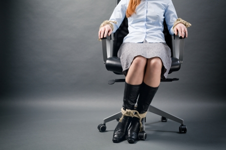 A dramatic photo of a young businesswoman tied with rope to an office chair. Imagens