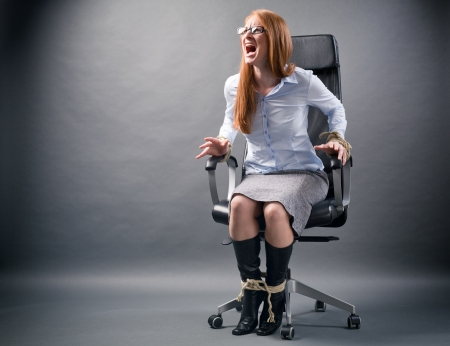 A young businesswoman confined to an office chair shouting for help and trying to free herself.