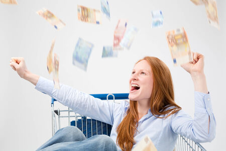 A young woman sitting in a shopping cart and cheering at a lot of paper money falling from above. photo
