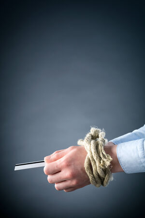 Two female hands tied up with rope holding a credit card, side view. photo