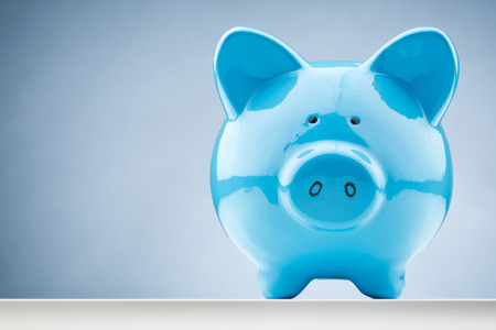 save money: Front closeup image of a blue piggy bank with copy space.