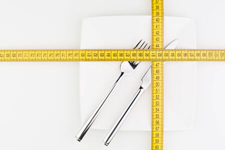 Top view of a white plate with a fork and a knife covered with a cross made of yellow measurement tape. photo