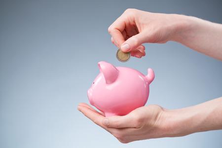 ピンクの貯金に 2 ユーロ コインを挿入する女性の手。