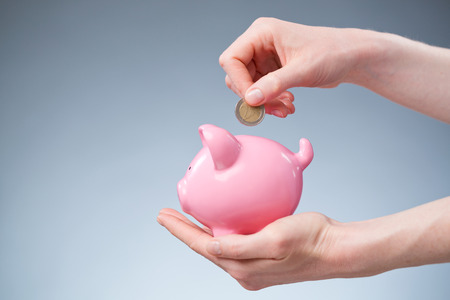A female hand inserting a two Euro coin into a pink piggy bank. photo