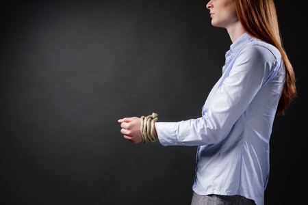 abducted: A young businesswoman with tied up hands before a dark background with dramatic light. Stock Photo