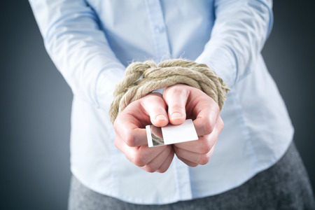 Een schuld concept of metafoor - een zakenvrouw met vastgebonden handen houden van een creditcard. Stockfoto - 25682033