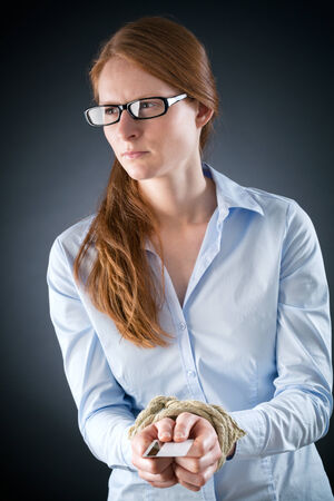 A sad woman with hands tied up with a rope holding a credit card and looking away. photo