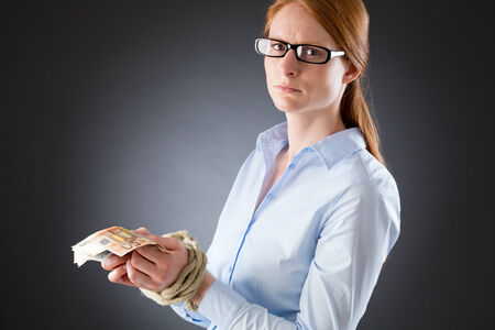 dependent: A sad woman dependent on money with tied hands holding on to Euro notes.