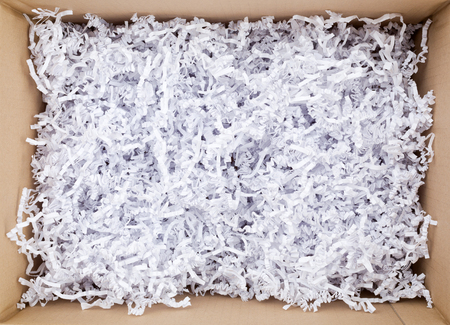 padding: Top view photo of an open mail parcel with wrinkled white padding paper of filling inside it.