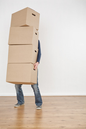A person carrying a heavy stack of moving boxes into an empty new house. photo