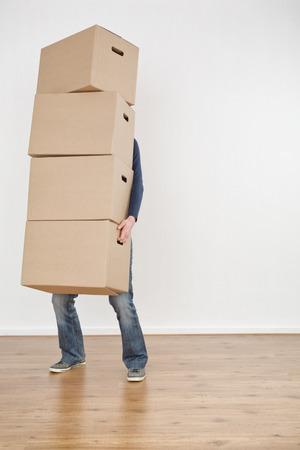 Az a személy, kezében egy nagy rakás mozgó dobozok egy üres új ház. Stock fotó
