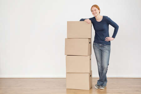 to unpack: Full length photo of a young woman standing next to a stack of storage or moving boxes and smiling. Stock Photo
