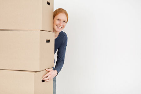 A happy and smiling young woman carrying moving boxes.