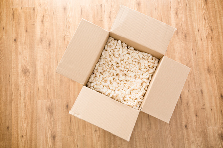 padding: Top view of an open carton box with foam filling or padding inside.