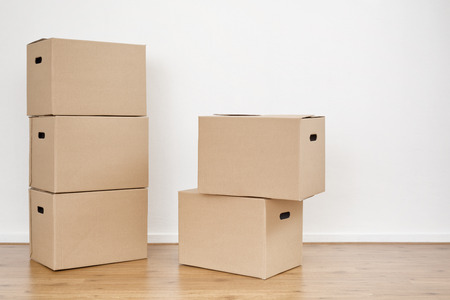 stacked up: Two stacks of moving boxes on the floor of an empty room with a white wall.