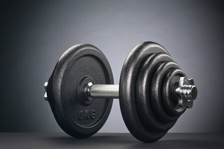 adjustable dumbbell: Dramatic image of a metal adjustable dumbbell with black discs.