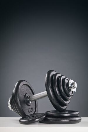 adjustable dumbbell: A dumbbell resting on a stack of black weight discs with copy space above it.