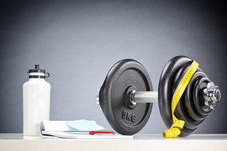 adjustable dumbbell: Accessories for fitness - water bottle, dumbbell and a notebook. Stock Photo
