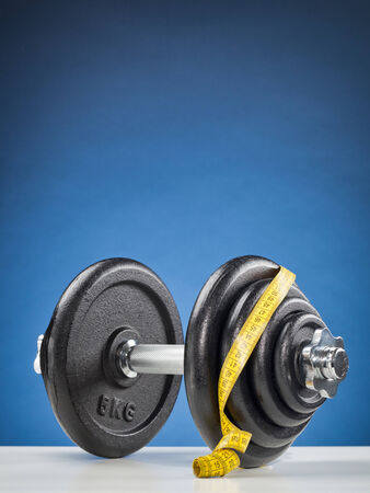 adjustable dumbbell: A heavy fitness dumbbell with yellow measuring tape over it. Stock Photo