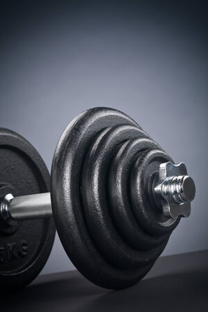 Fitness equipment - closeup image of a heavy iron dumbbell with black weight discs.