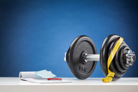 adjustable dumbbell: Dumbbell with measuring tape and a notebook on a white surface with blue background.