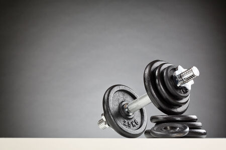 adjustable dumbbell: Bodybuilding or fitness equipment - a dumbbell resting on a stack of black weight discs.