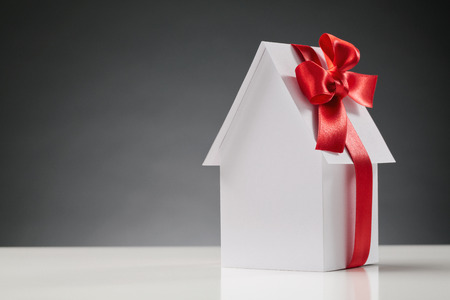 新しいホームのコンセプトを購入 - それを赤いリボンで新しいホワイト ペーパー家。