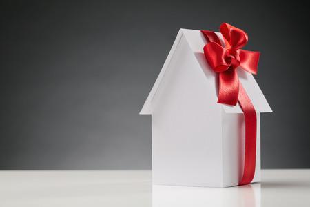 Een nieuwe white paper huis met een rood lint op het - het kopen van een nieuw huis concept. Stockfoto - 27570719