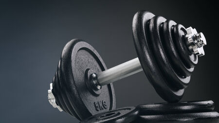 adjustable dumbbell: Weight lifting - a heavy dumbbell resting on a stack of black discs.