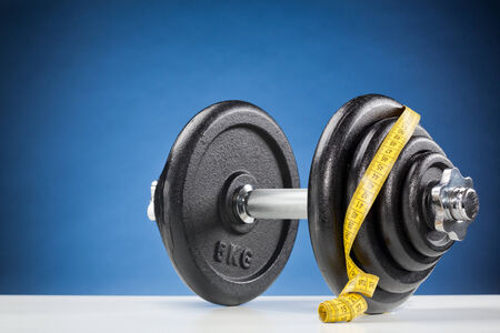 adjustable dumbbell: Fitness concept - dumbbell with measuring tape on a white surface with blue background.