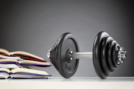 Dumbbell with black discs standing on a table next to a stack of open books. Stock Photo